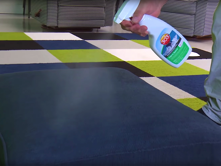 Spraying 303 Fabric Guard on a sofa cushion to add stain protection