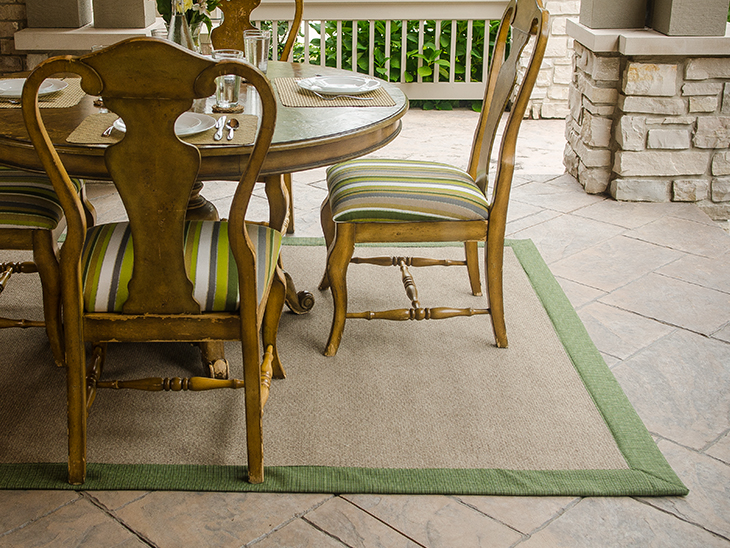 Fabric trimmed outdoor rug installed under an outdoor dining table