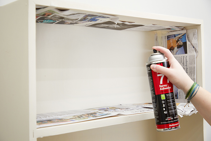 Carefully apply adhesive spray to the back of one shelf.